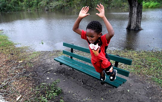 Mamarion Grady, 5, plays on bench at a park where the Neuse River has flooded a portion of the downtown Kinston, NC park on Sunday, Sept. 16 ,2018.