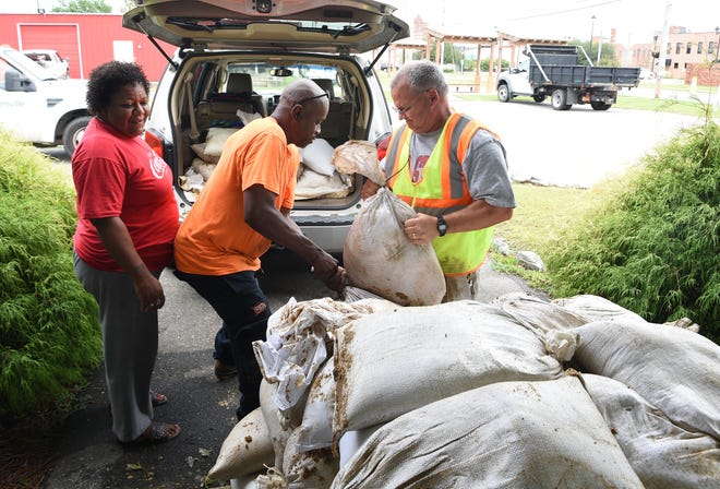 Kevin Heifferson of the City of Greenville, NC helps load sandbags for Temika Bernard in Kinston, NC on Sunday, Sept. 16 ,2018. Bernard wanted the sandbags in case of flooding at her home.