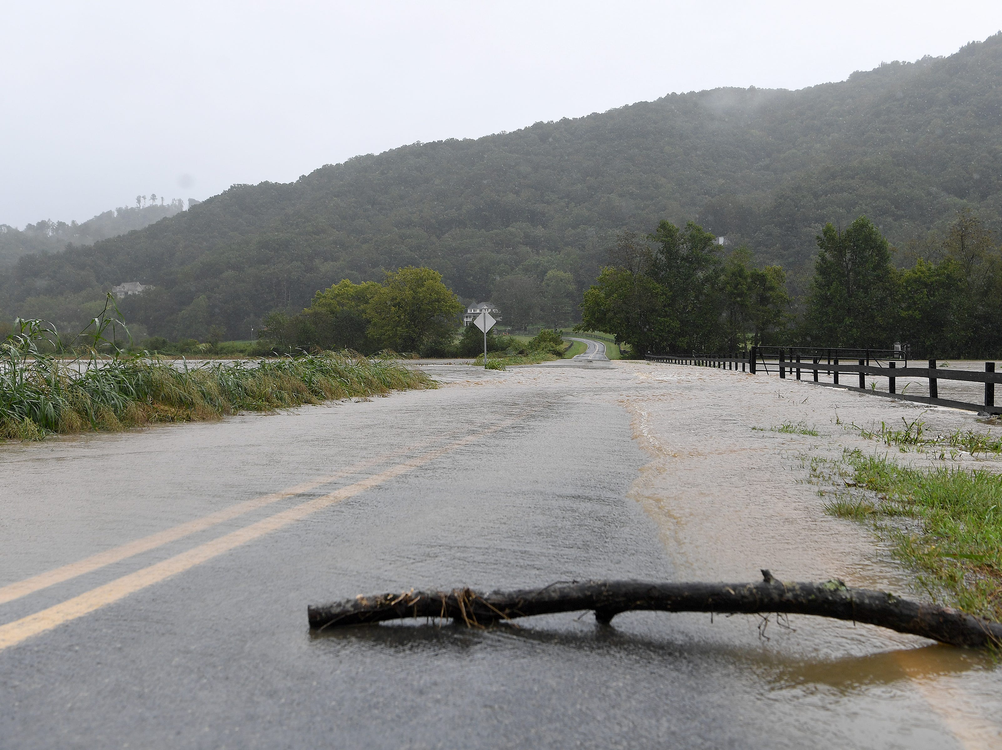 A stick was placed on Lower Brush Creek Road to monitor the rate of flooding as Cane Creek jumps its banks and covers the road in Fletcher with water on Sept. 16, 2018. Hurricane Florence, now downgraded to a tropical depression brought sustained rain to the area.