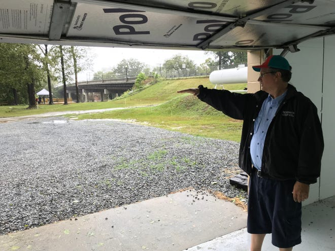 Craig Williams, owner of Deep Creek Outfitters in Fayetteville, North Carolina, stands in his building Sunday, showing how high floodwaters rose in 2016 during Hurricane Matthew. Forecasters have predicted worse flooding for the area by Tuesday from Tropical Depression Florence.