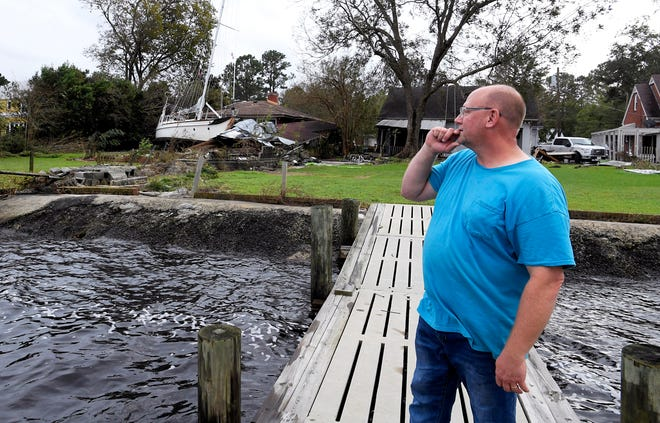 New Bern, NC resident Todd Gratz surveys his neighbors' backyard on Sunday, Sept. 16, 2018 where Hurricane Florence heavy rains and flooding washed a sailboat into his neighbors's backyard.