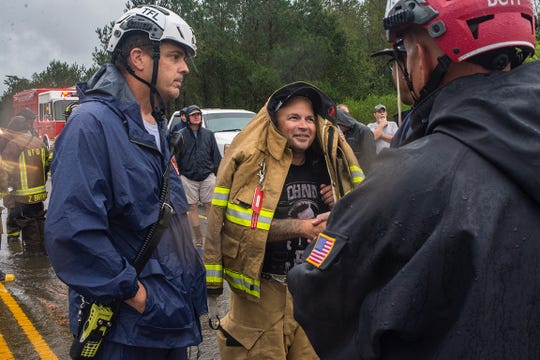 Shane Rhodes, assistant chief of the Beulaville Fire Department, uses his coat to shield himself from heavy rain at the scene of a swift-water rescue Saturday afternoon.