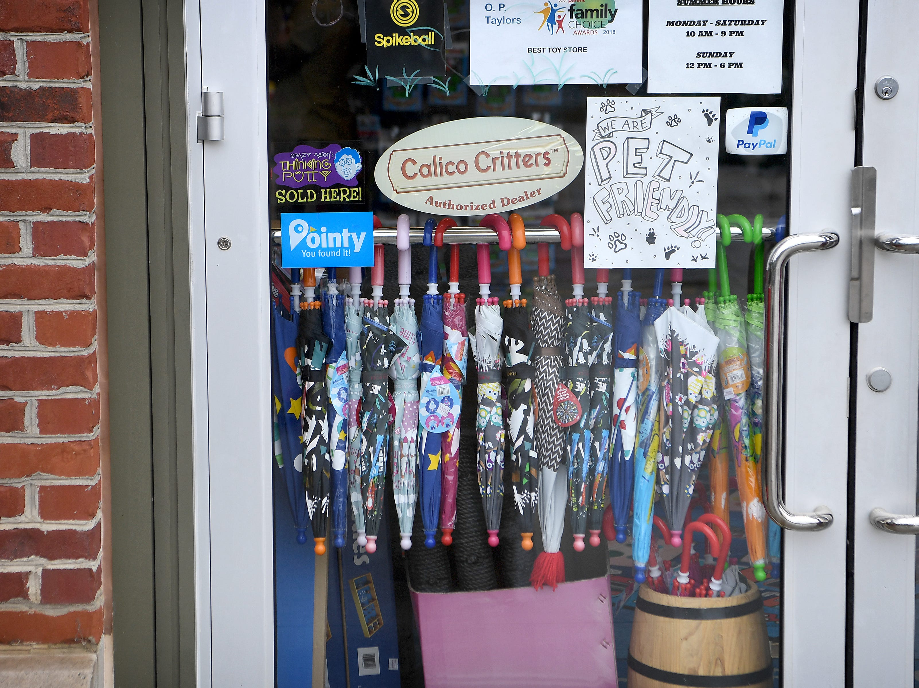 Children-sized umbrellas hang on the door of O.P. Taylor's toy store in Biltmore Park as rain caused by Hurricane Florence, now downgraded to a tropical depression, falls on the area on Sept. 16, 2018.