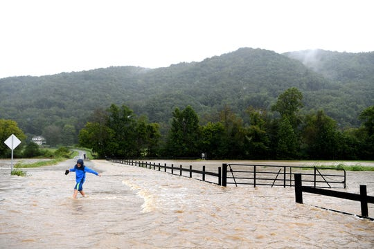 Thomas Klepper, 12, checks out the flooding near his house as Cane Creek jumps its banks and covers Lower Brush Creek Road in Fletcher with water on Sept. 16, 2018. Hurricane Florence, now downgraded to a tropical depression brought sustained rain to the area.