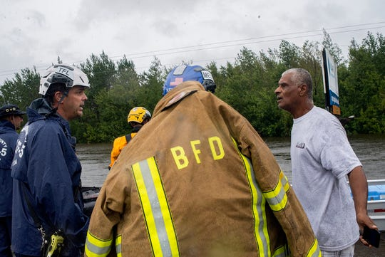 California Task Force Five Chief Craig Covey speaks with a Beulaville resident at the scene of a swift-water rescue Saturday afternoon. The man was asking for the rescuers to ferry his wife across a flooded road. The risk would be too great, Covey said, declining the request.