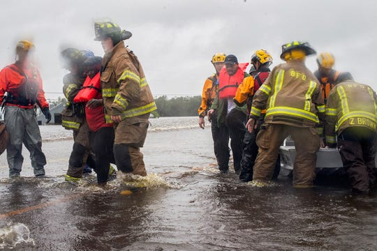 Swift-water rescuers from California work with Beulaville fire fighters to get a recently evacuated couple out of the shallow-bottom boats in which they were rescued.