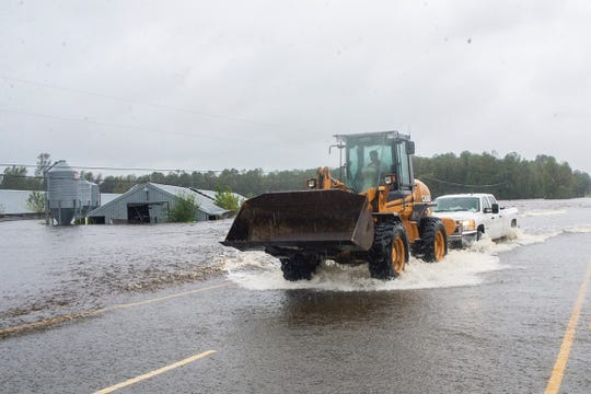 A Beulaville resident uses a front loader to tow a truck through high fast-moving water that covered N.C. 24 Saturday.