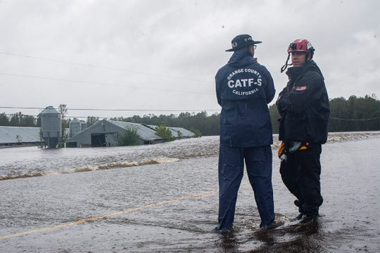 Dave Orr, left, and Davis Doty, right, look at two chicken houses submerged in flood waters in Beulaville, N.C.