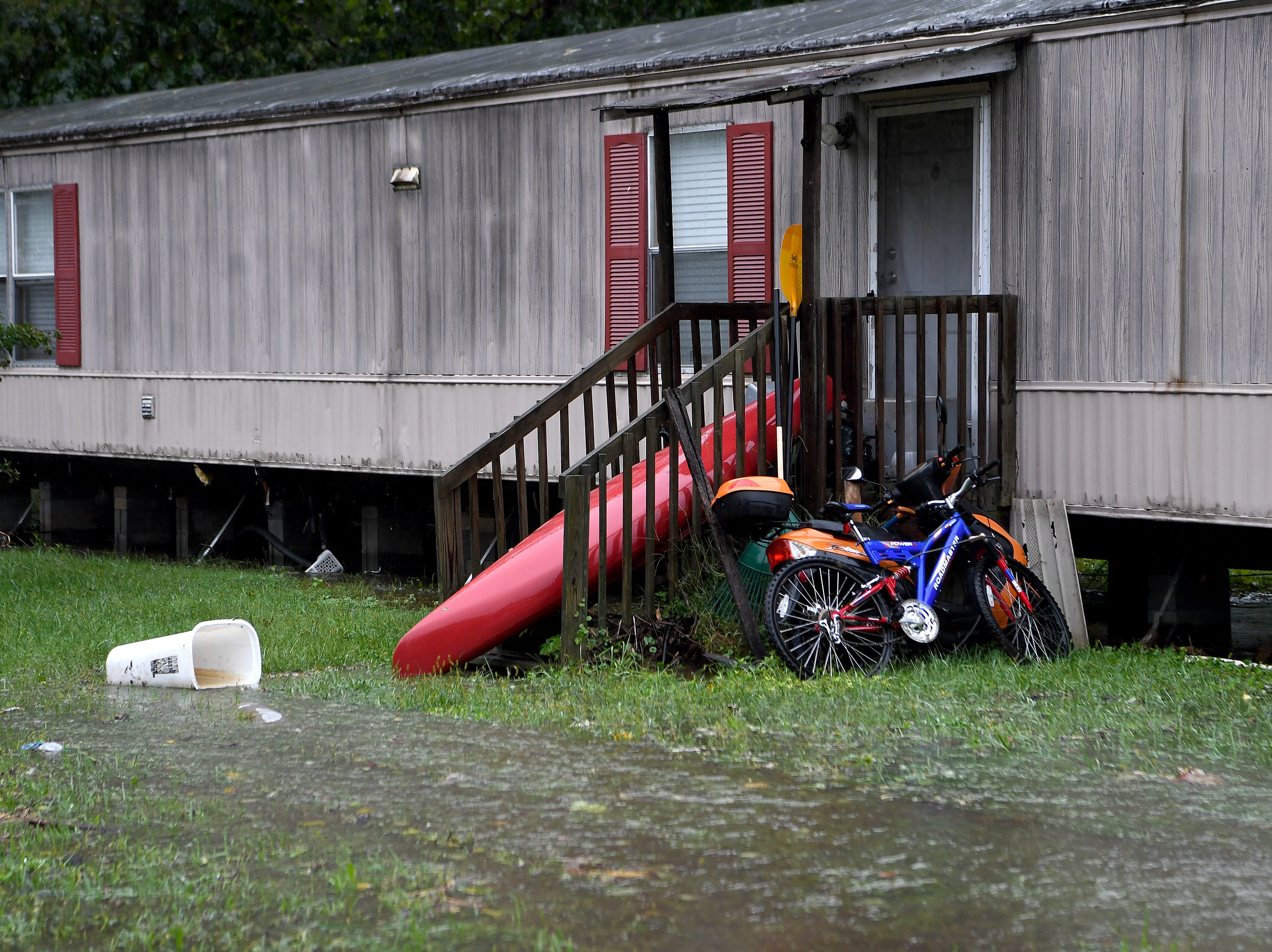 A boat sits on a front porch as water from Flat Creek flooded into the Portman Villas Mobile Home Park in Black Mountain and continued to rise forcing evacuations of homes on Sept. 16, 2018.