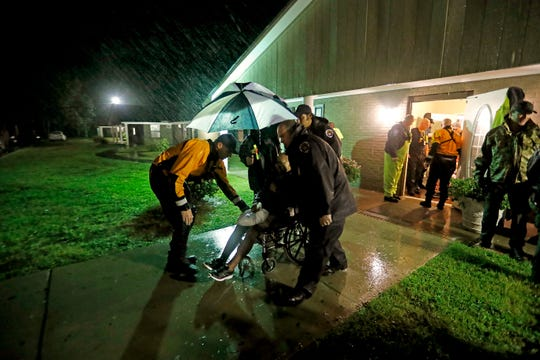 Members of the Nebraska Task Force 1 urban search and rescue team help load an elderly resident onto a bus as they evacuate an assisted living facility to a church as a precaution against potential flooding the city could see from tropical storm Florence in Fayetteville, N.C., Saturday, Sept. 15, 2018. (AP Photo/David Goldman)