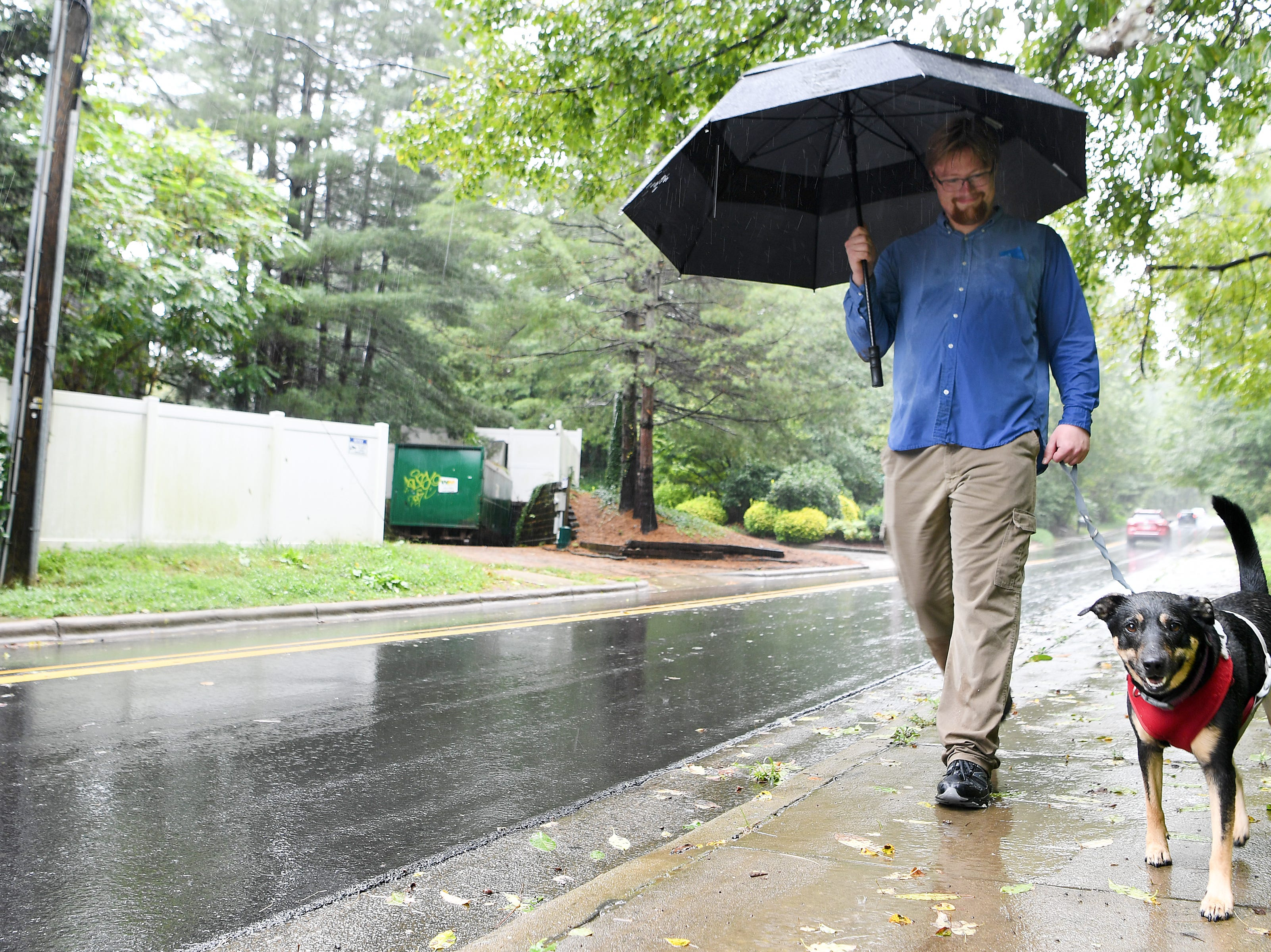 """Anders Joura walks his dog, Maizy, down Beverly Road in Haw Creek as rains from Hurricane Florence, now downgraded to a tropical depression, soaked the area on Sept. 16, 2018. Joura said that the long, wet walk was """"very much her idea."""""""