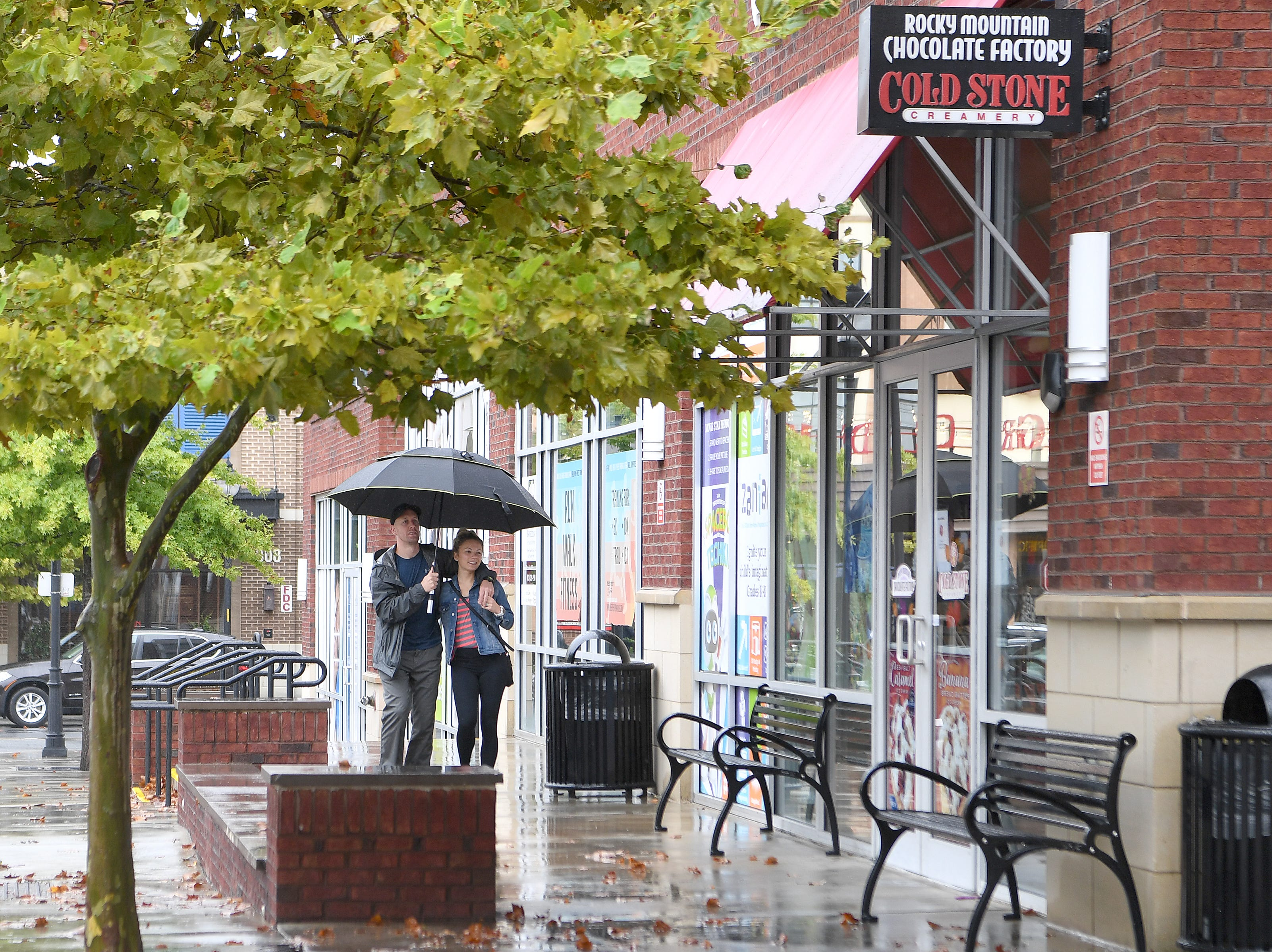 A pair share an umbrella in Biltmore Park as gentle rain from Hurricane Florence, now downgraded to a tropical depression falls in the area on Sept. 16, 2018.