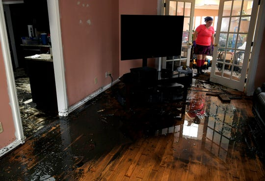 New Bern, NC resident Cynthia Downes walks through her home on Sunday, Sept. 16, 2018 where flood water reached inside her home during Hurricane Florence.