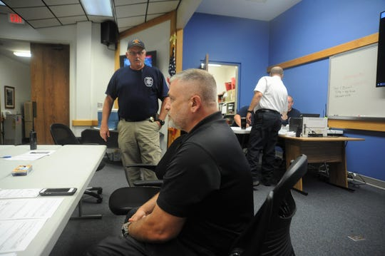 Public works director Jamey Matthews, sits at the table in the Public Safety Room as Black Mountain fire chief Steve Jones talks about the impacts of Tropical Depression Florence.