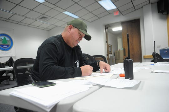 Black Mountain police chief Shawn Freeman works on paper work in the Public Safety Room in between the police and fire departments. The room will serve as the base for the town's Emergency Operations Center until Tuesday.