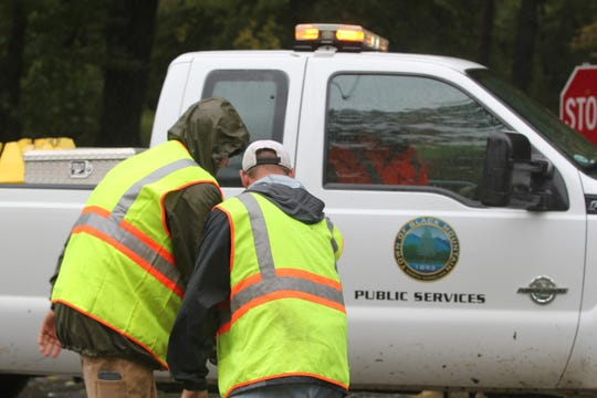 Black Mountain Public Services crews place a barricade warning against entering Portman Villas Mobile Home Park after residents who live near Flat Creek were evacuated on Sept. 16.