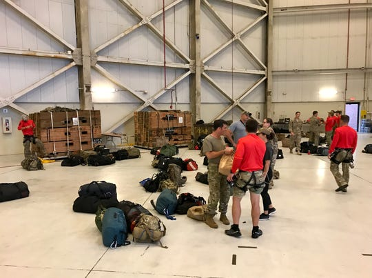 Red-shirted pararescuemen with the 920th Rescue Wing stow gear inside a hangar at Joint Base Charleston.