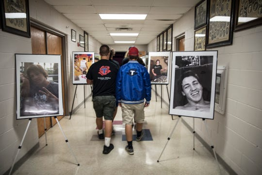 Attendees of the 2018 Tristan Miller Music Fest walk through pictures that highlighted Tristan's life as they enter the Zane Trace cafeteria to hear the various musical bands play.
