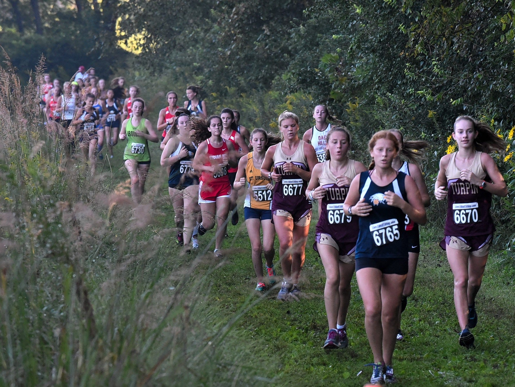 The trail of runners is long as the ladies run at the 2018 Milford Cross Country Invitational, Sept. 15, 2018.