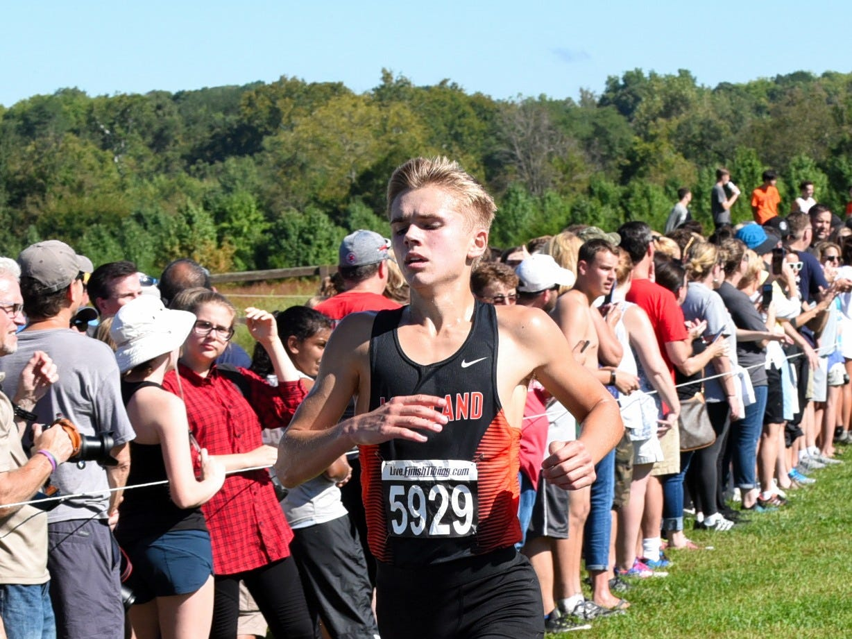 Loveland's Greg Ballman crosses the purple finish in third place in the boys varsity 5K race at the 2018 Milford Cross Country Invitational, Sept. 15, 2018.