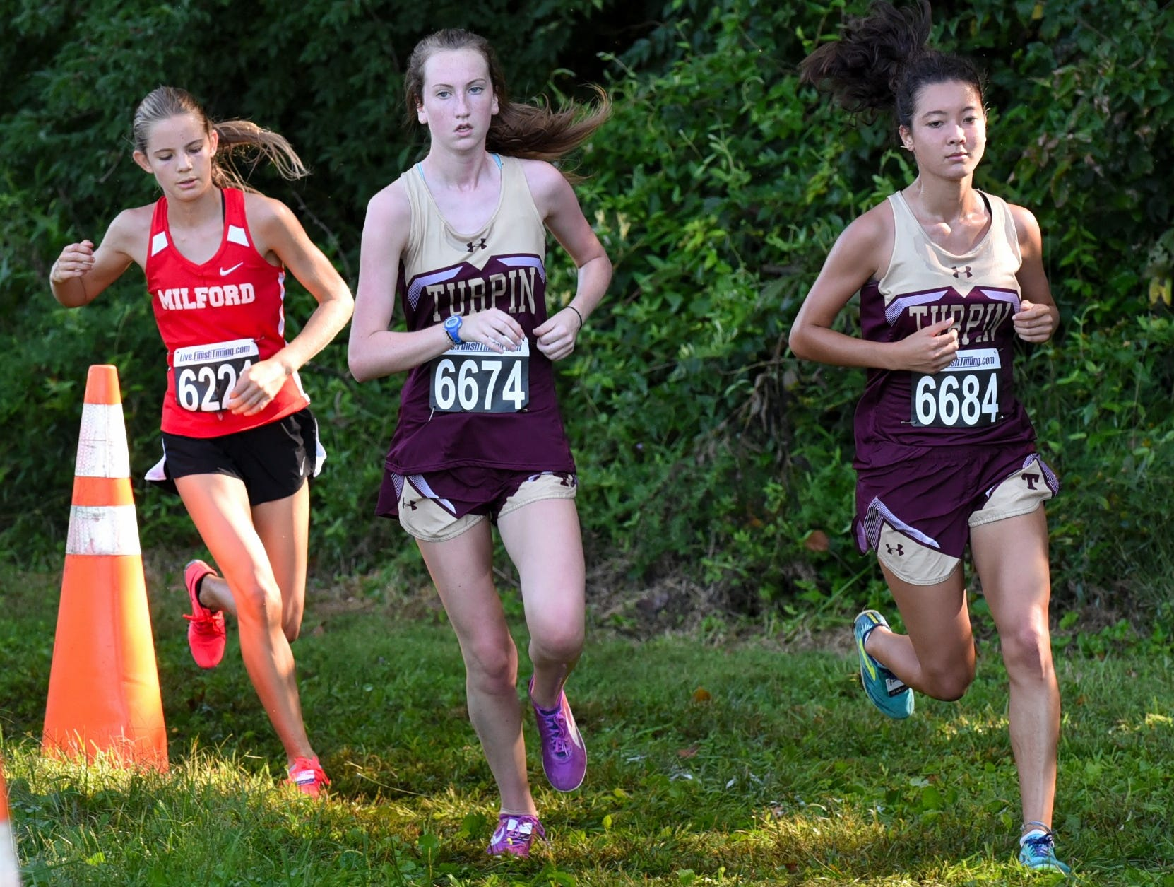 Jayne Maxwell and Isabel Shim of Turpin run in tandem in the Varsity Girls 5K race at the 2018 Milford Cross Country Invitational, Sept. 15, 2018.