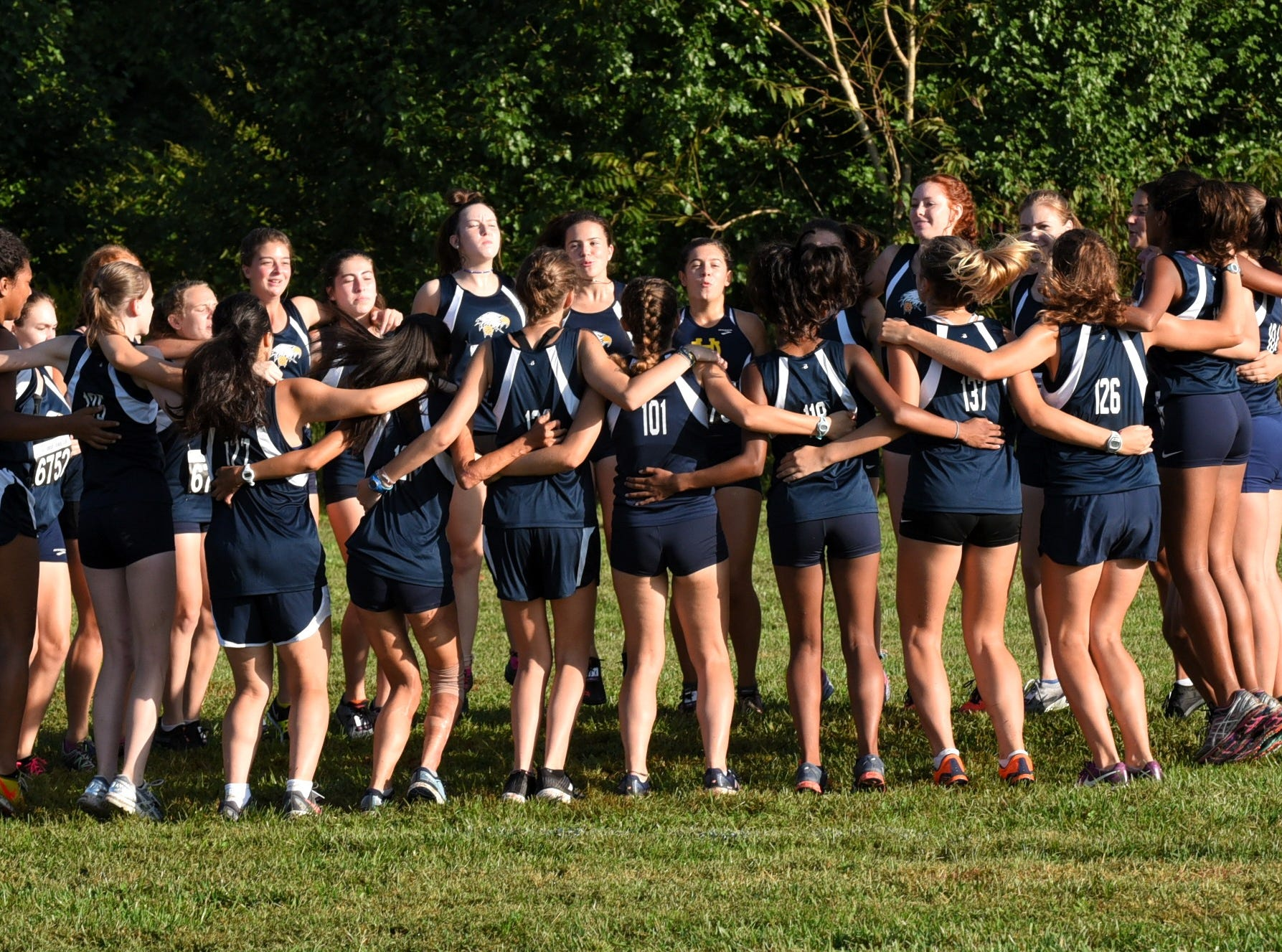 Walnuts Hills lady runners get hyped prior to running at the 2018 Milford Cross Country Invitational, Sept. 15, 2018.