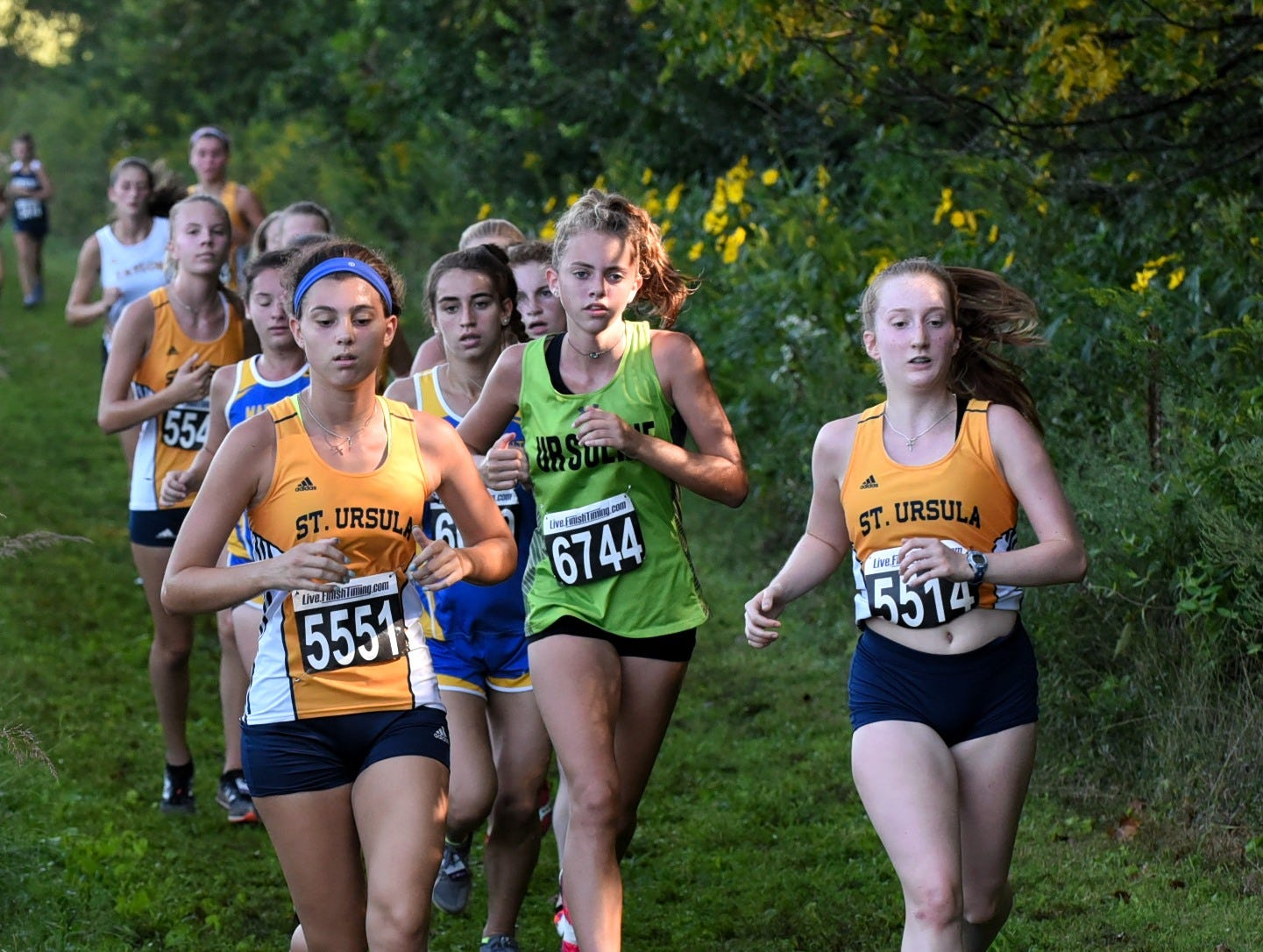 Josie Podoto and Deirde Carroll of St. Ursula and Leigha Timberlake of Ursuline lead a group of ladies down a back straight at the 2018 Milford Cross Country Invitational, Sept. 15, 2018.