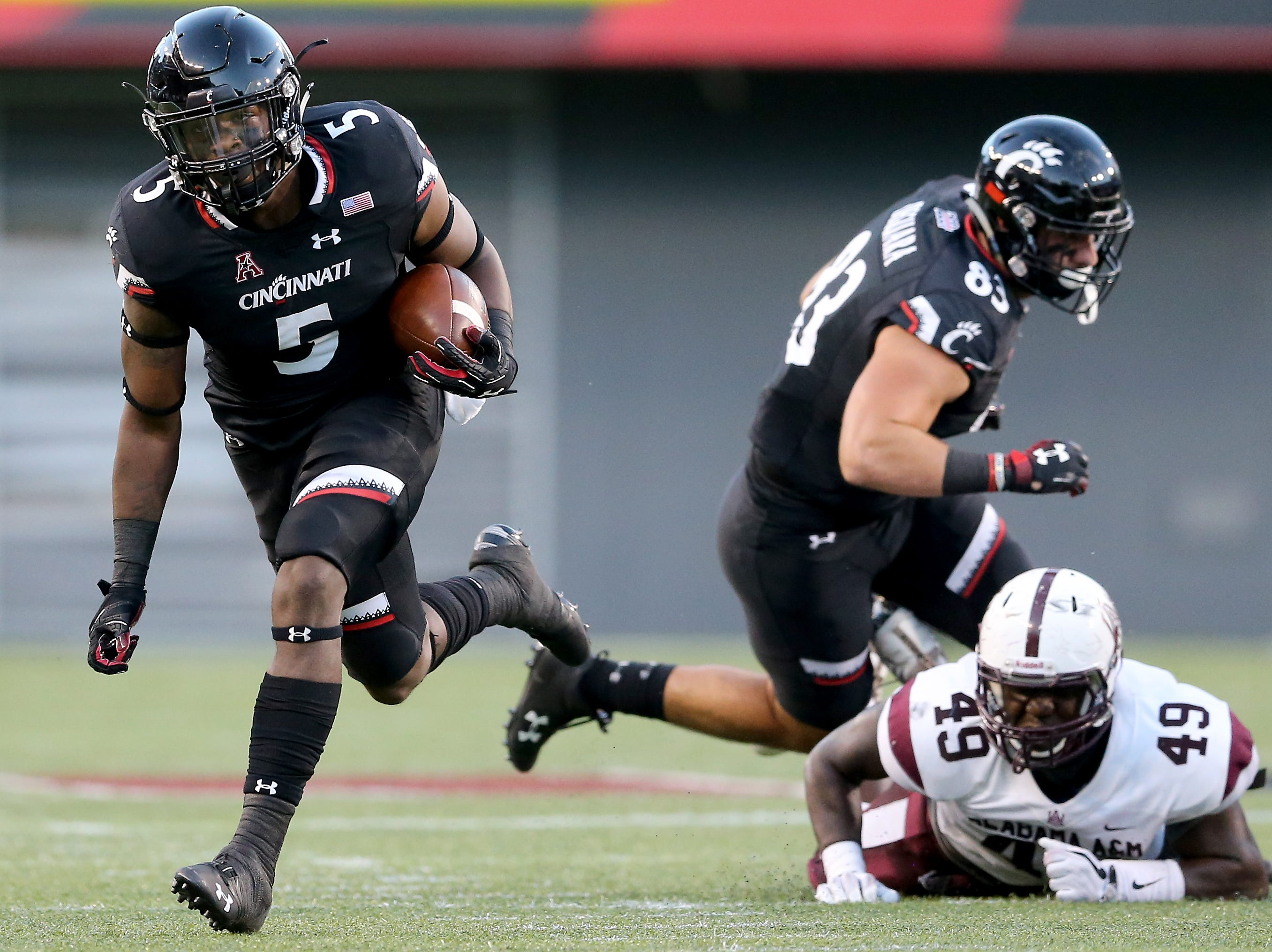 Cincinnati Bearcats running back Tavion Thomas (5) carries the ball as Alabama A&M Bulldogs defensive end Solomon Hunter (49) can't make the tackle in the first quarter during a college football game between the Cincinnati Bearcats and the Alabama A&M Bulldogs, Saturday, Sept. 15, 2018, at Nippert Stadium in Cincinnati.