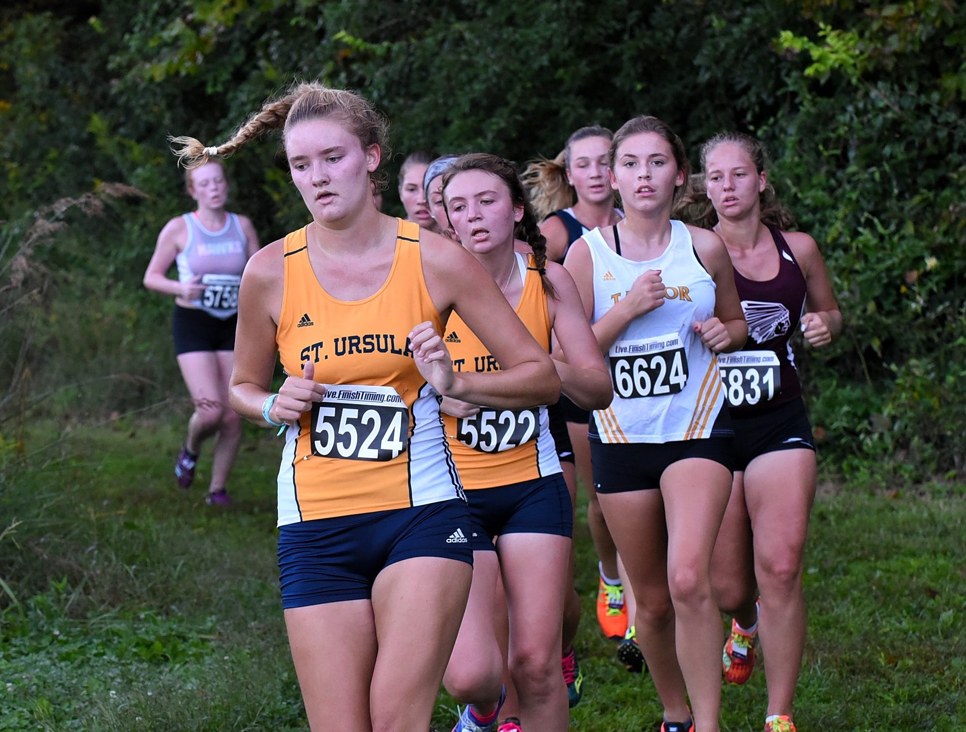 St.Ursula's Claire Earls and Hanna Durbin lead a pack of runners around a corner in the forest while running at the 2018 Milford Cross Country Invitational, Sept. 15, 2018.