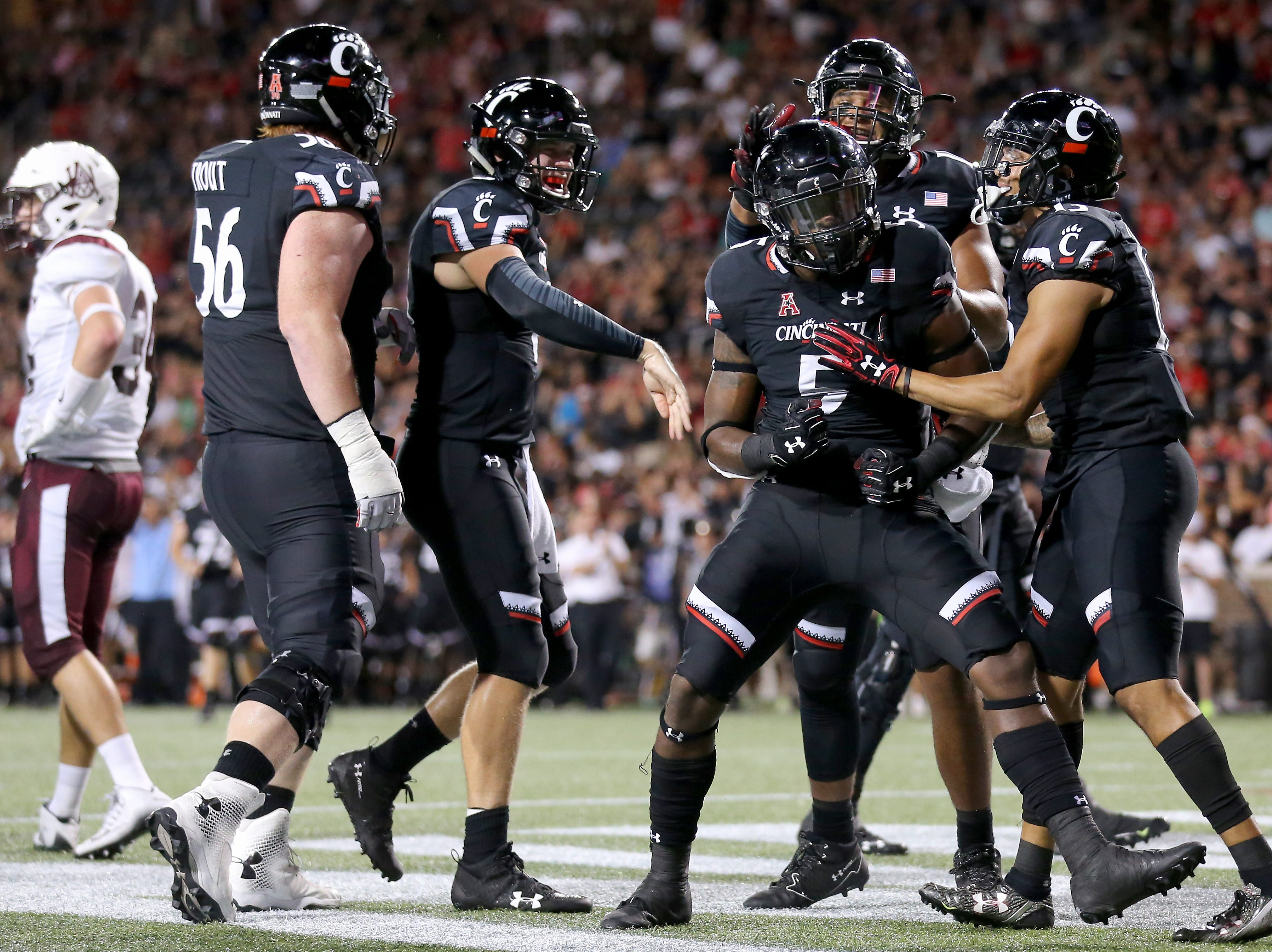 Cincinnati Bearcats running back Tavion Thomas (5), center, is congratulated after scoring a touchdown in the second quarter during a college football game between the Cincinnati Bearcats and the Alabama A&M Bulldogs, Saturday, Sept. 15, 2018, at Nippert Stadium in Cincinnati.