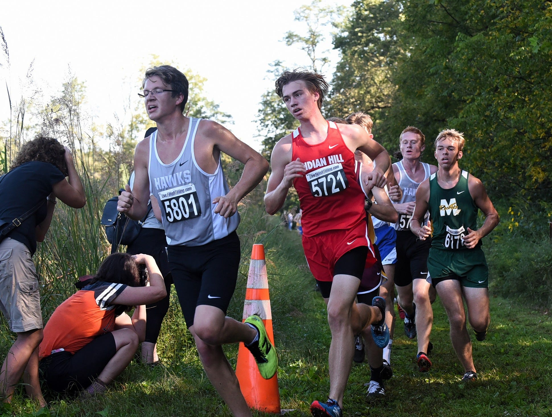 Lakota East's Troy Temelis, Indian Hill's Tommy Tauer and Hunter Evans of McNicholas take a hard turn in the Boys varsity 5K race at the 2018 Milford Cross Country Invitational, Sept. 15, 2018.