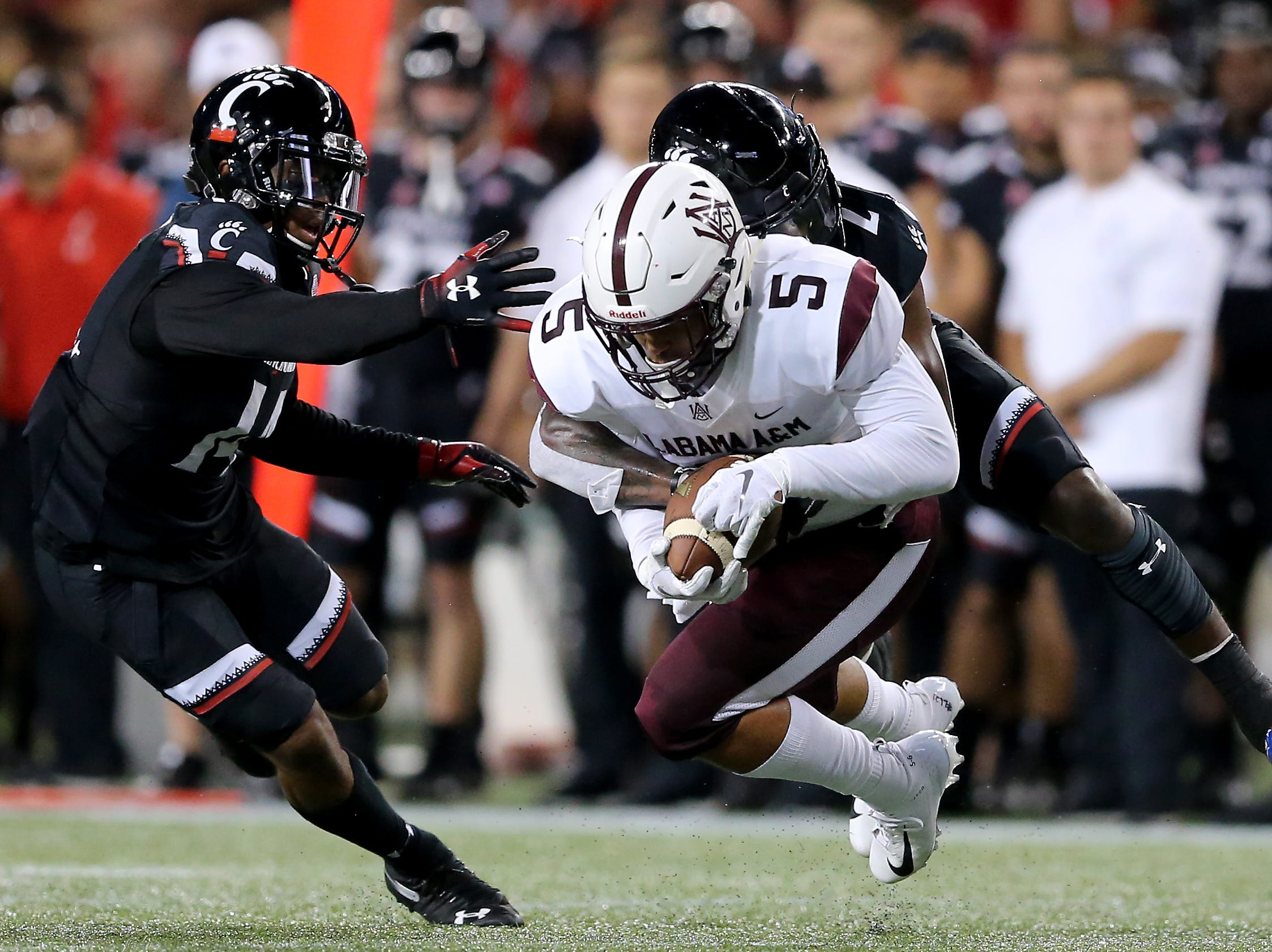 Cincinnati Bearcats cornerback Tyrell Gilbert (2) tackled Alabama A&M Bulldogs wide receiver Isaiah Bailey (5) in the second quarter during a college football game between the Cincinnati Bearcats and the Alabama A&M Bulldogs, Saturday, Sept. 15, 2018, at Nippert Stadium in Cincinnati.