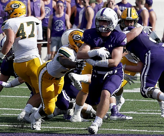 Elder running back Luke Masminster wraps up the ball as he carries against St. Edward during their game at The Pit in Cincinnati Saturday, Sept. 15, 2018.