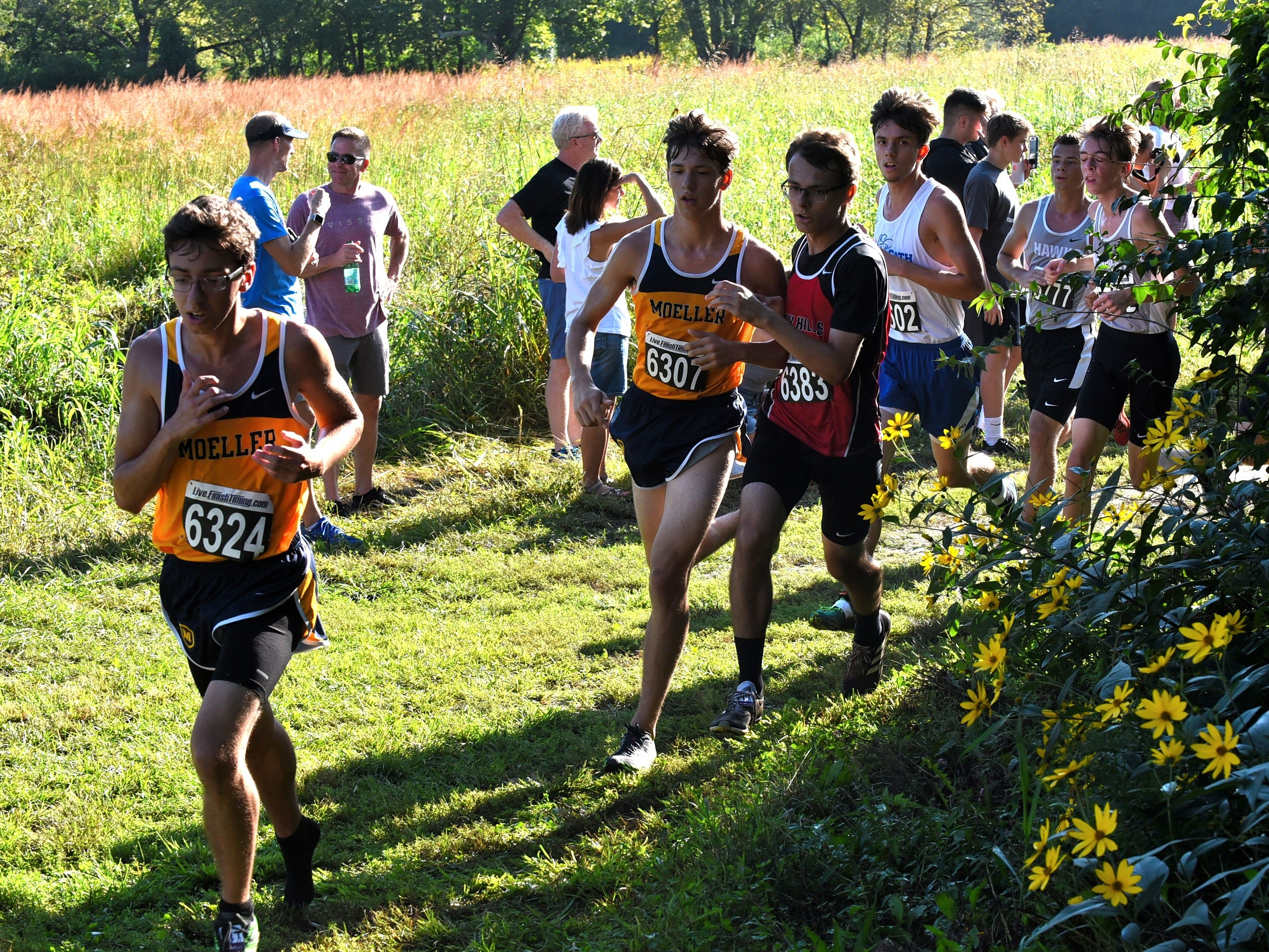Moeller runners lead a small pack past a flowery turn at the 2018 Milford Cross Country Invitational, Sept. 15, 2018.