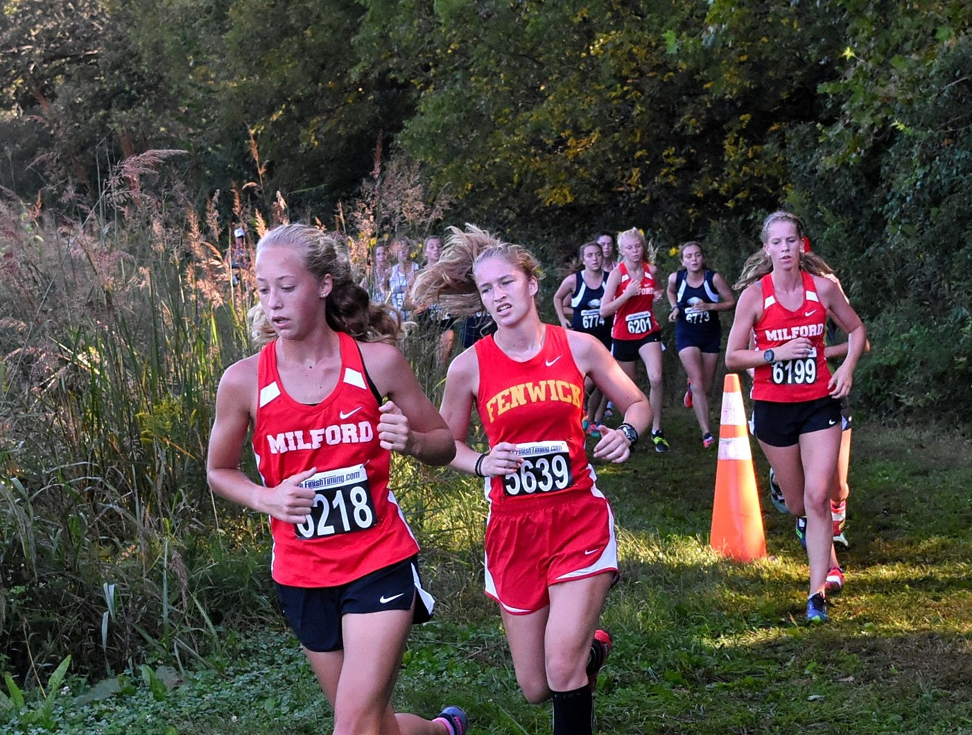 Milford's Emily Rodeffer, Fenwick's Hannah Tebbe and Emma Beck of Milford lead a group of ladies to the half way mark while running at the 2018 Milford Cross Country Invitational, Sept. 15, 2018.