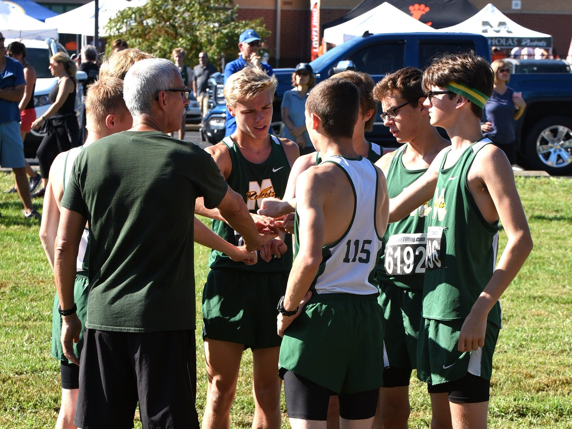 McNicholas runners huddle up prior to the boys varsity 5K race at the 2018 Milford Cross Country Invitational, Sept. 15, 2018.