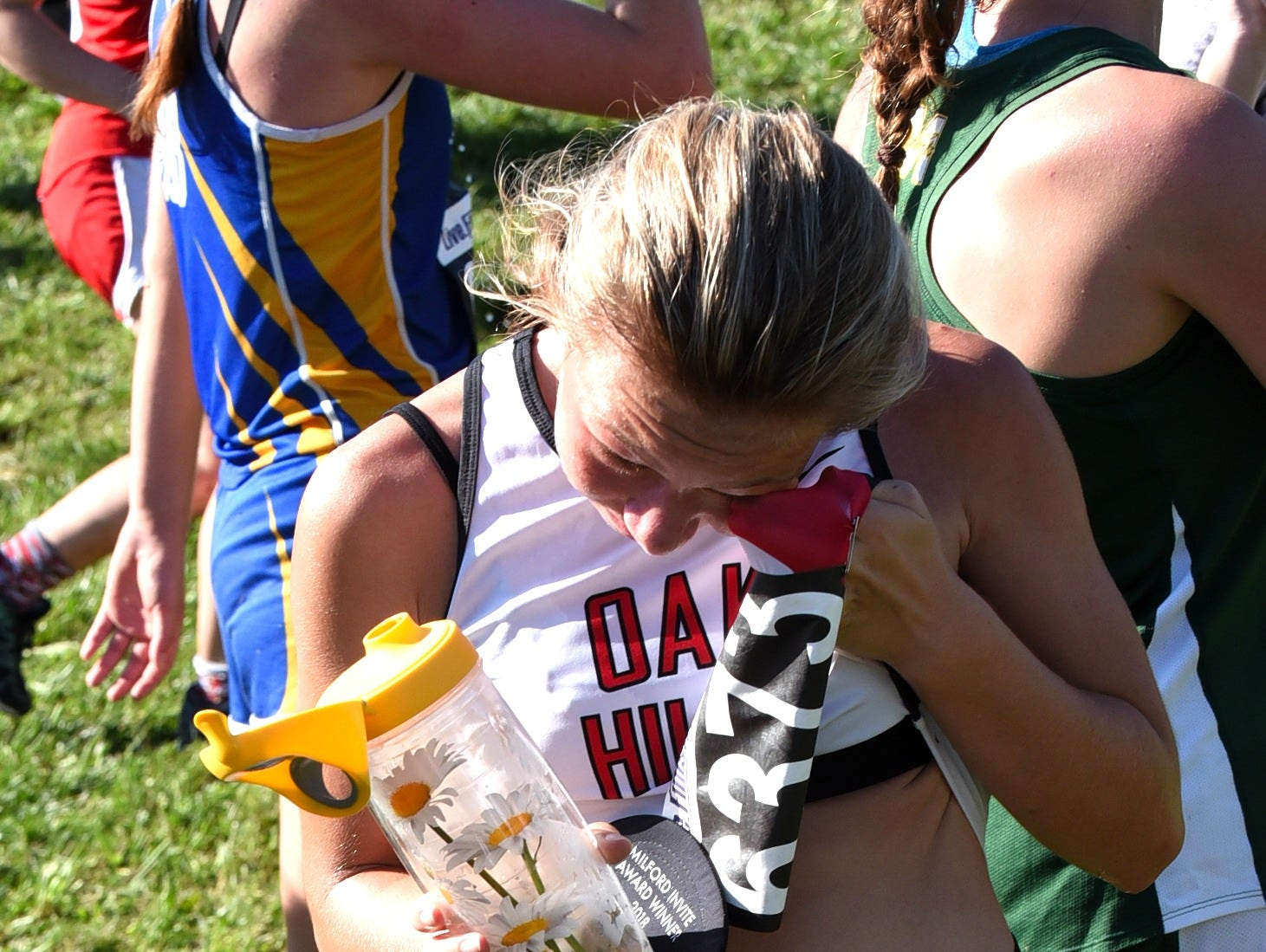 Emma Lucas wipes the sweat off of her brow after finishing strong in the Varsity girls 5K race at the 2018 Milford Cross Country Invitational, Sept. 15, 2018.