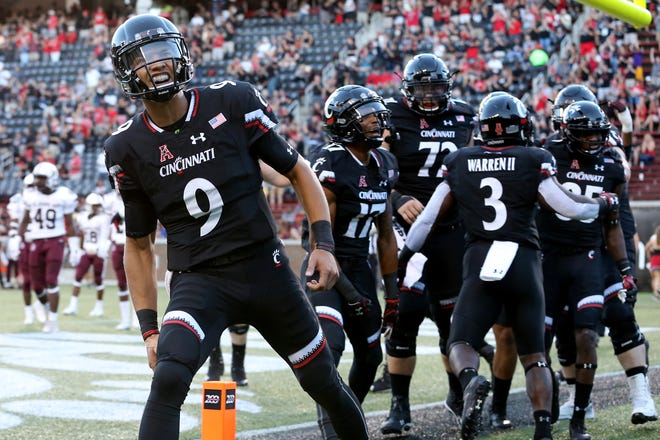 Cincinnati Bearcats quarterback Desmond Ridder (9), far left, celebrates a touchdown pass to Cincinnati Bearcats wide receiver Thomas Geddis (85), far right, in the first quarter during a college football game between the Cincinnati Bearcats and the Alabama A&M Bulldogs, Saturday, Sept. 15, 2018, at Nippert Stadium in Cincinnati.