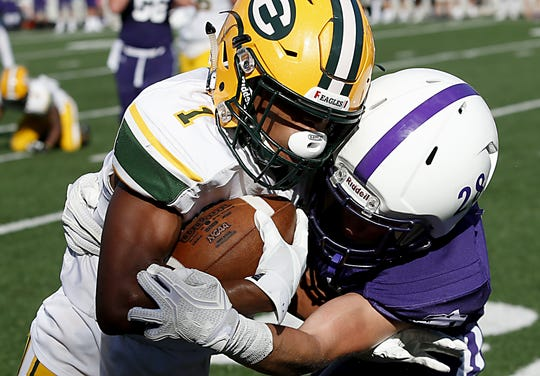 Elder defensive back Steven Seger puts a hit on St. Edward's Quintel Kent during their game at The Pit in Cincinnati Saturday, Sept. 15, 2018.
