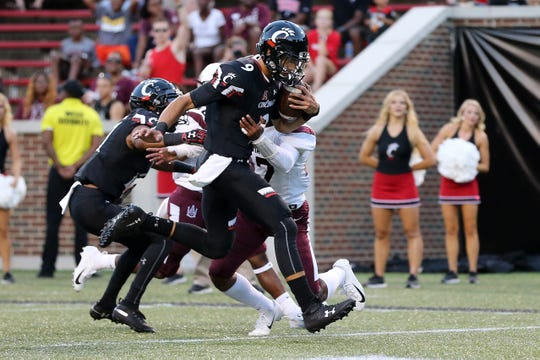 Cincinnati Bearcats quarterback Desmond Ridder (9), center, runs for a touchdown run in the first quarter during a college football game between the Cincinnati Bearcats and the Alabama A&M Bulldogs, Saturday, Sept. 15, 2018, at Nippert Stadium in Cincinnati.