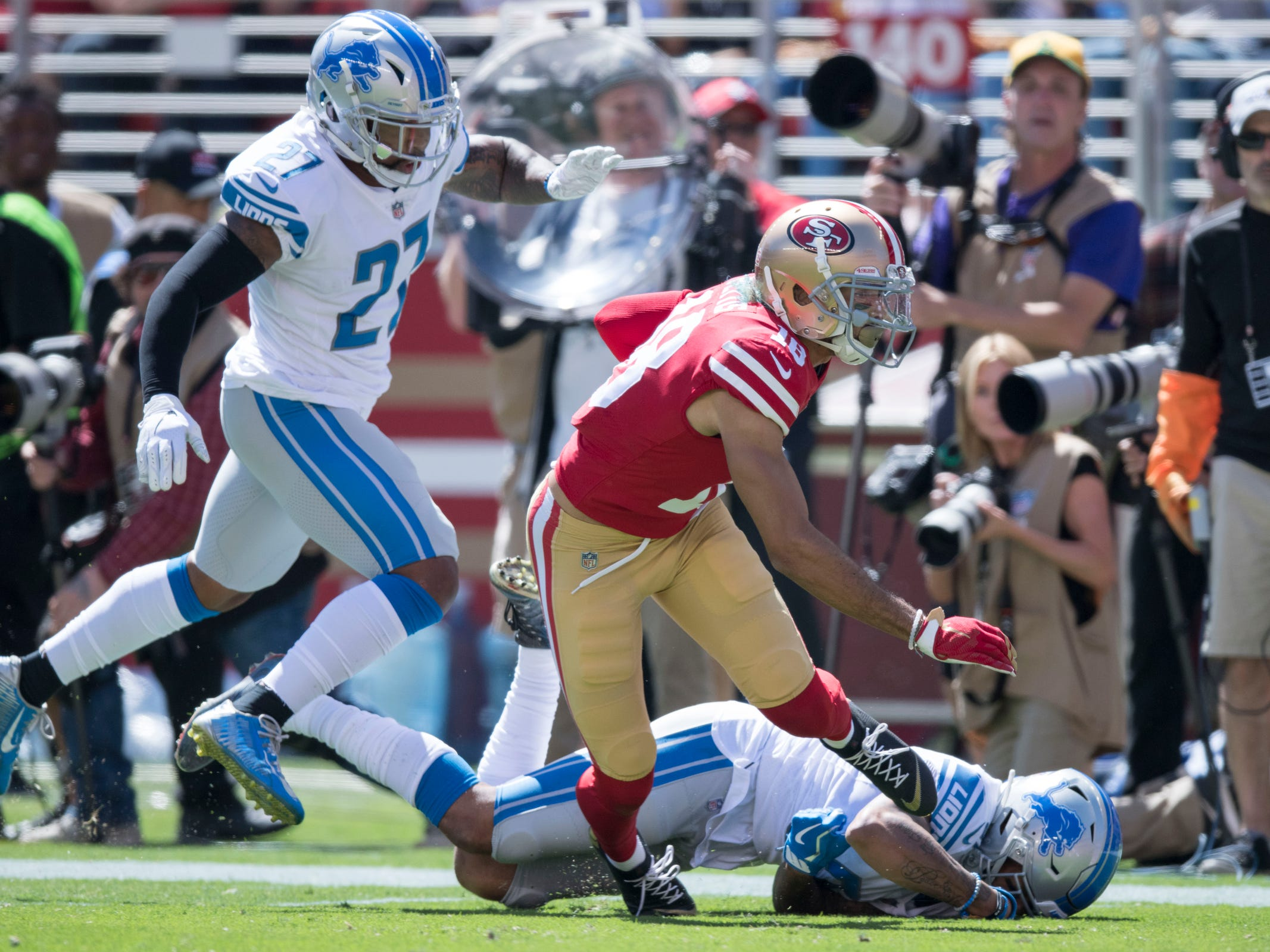 49ers wide receiver Dante Pettis runs with the football against Lions cornerback Teez Tabor (31) and defensive back Glover Quin (27) during the first quarter on Sunday, Sept. 16, 2018, in Santa Clara, Calif.