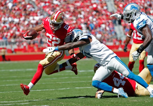 49ers running back Matt Breida runs with the ball as Lions defensive back Nevin Lawson tries to stop him during the first half on Sunday, Sept. 16, 2018, in Santa Clara, Calif.