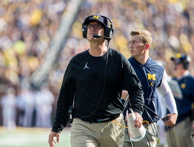 Michigan head coach Jim Harbaugh walks the sideline looking up at the scoreboard in the second quarter.