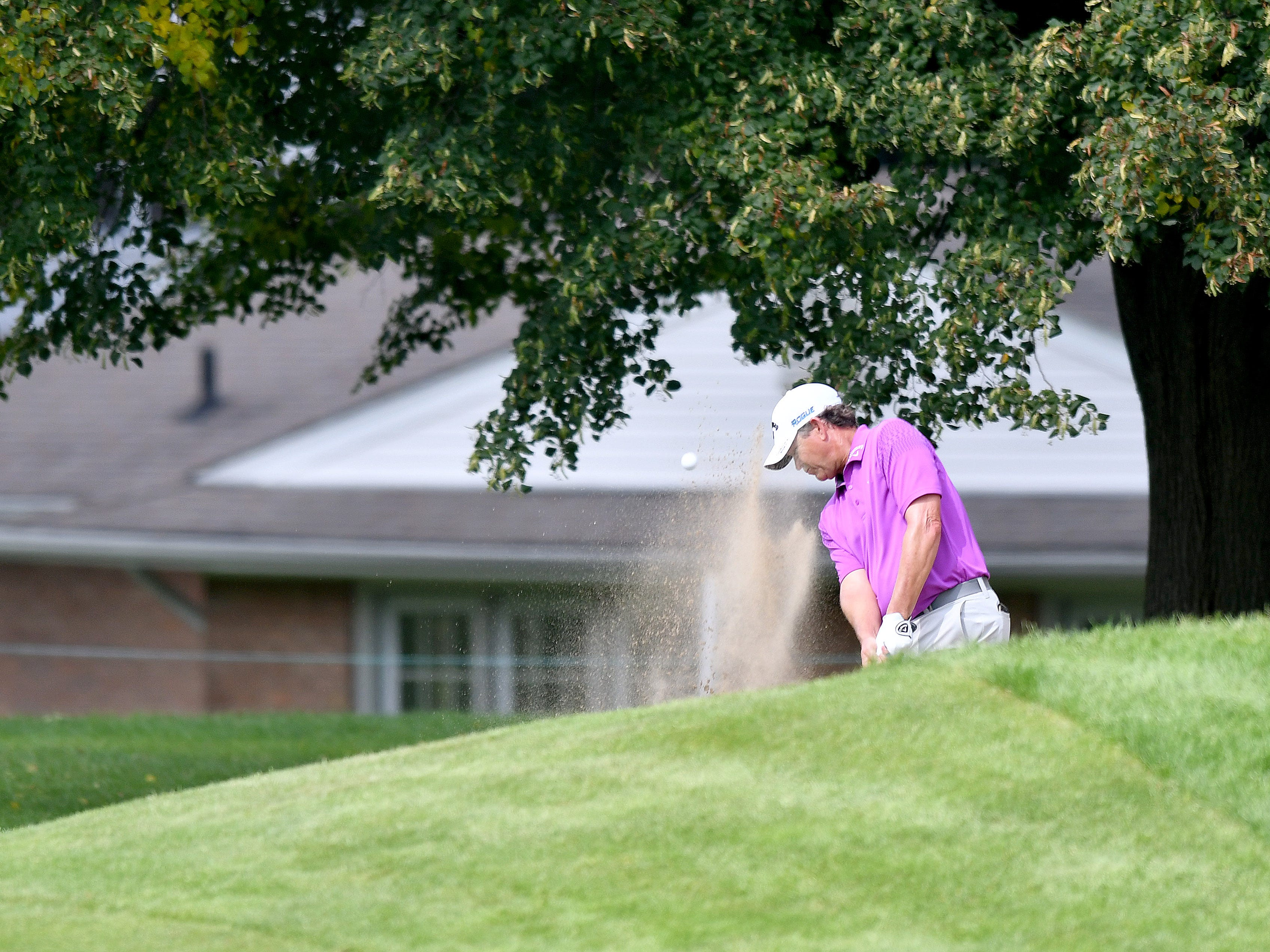 Lee Janzen hit out of a fairway bunker on the first hole at the Ally Challenge.