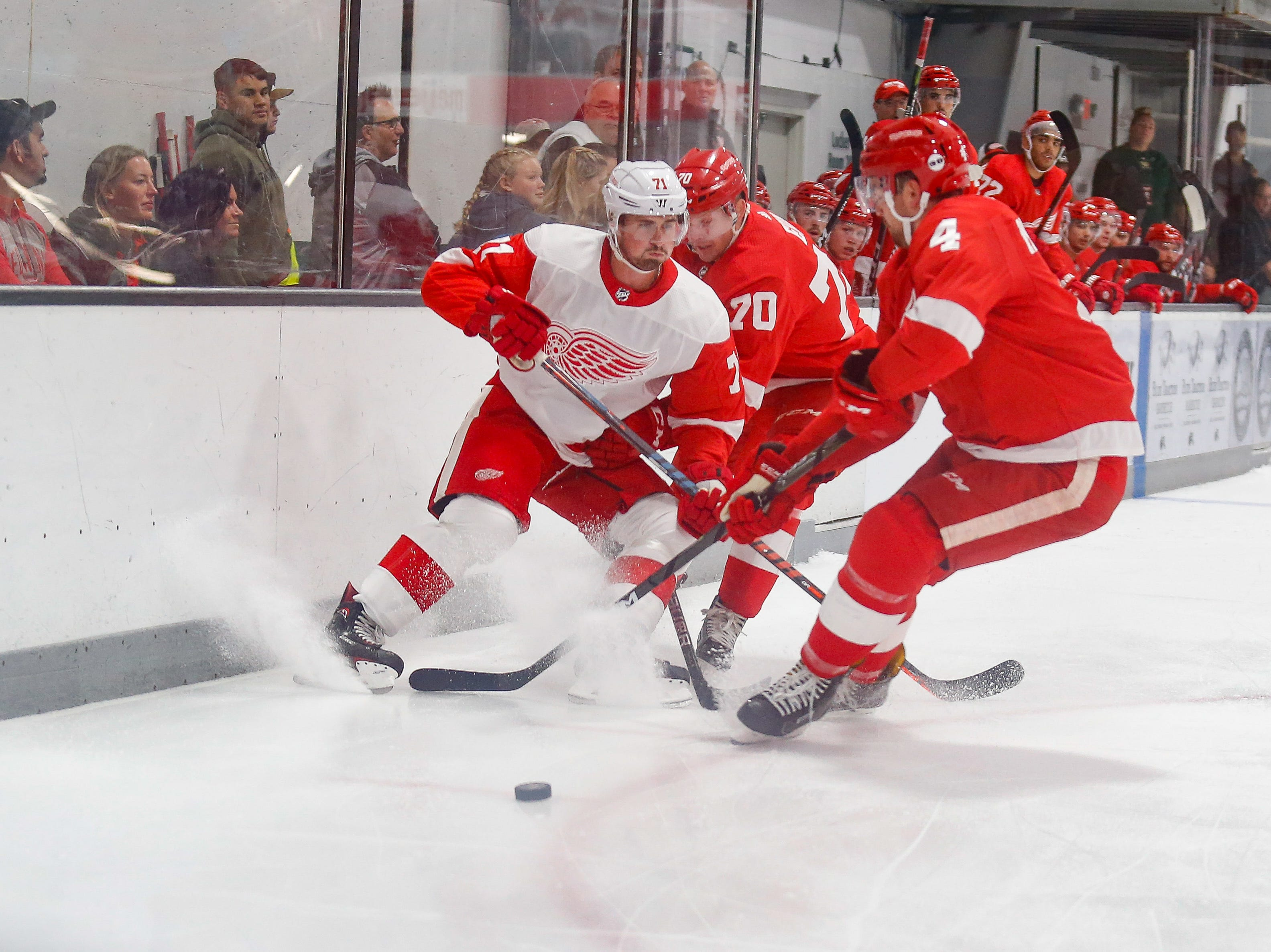 Christoffer Ehn (70) and Dylan McIlrath (4) converge on Dylan Larkin (71) as he tries to bring the puck into Team Red's zone.