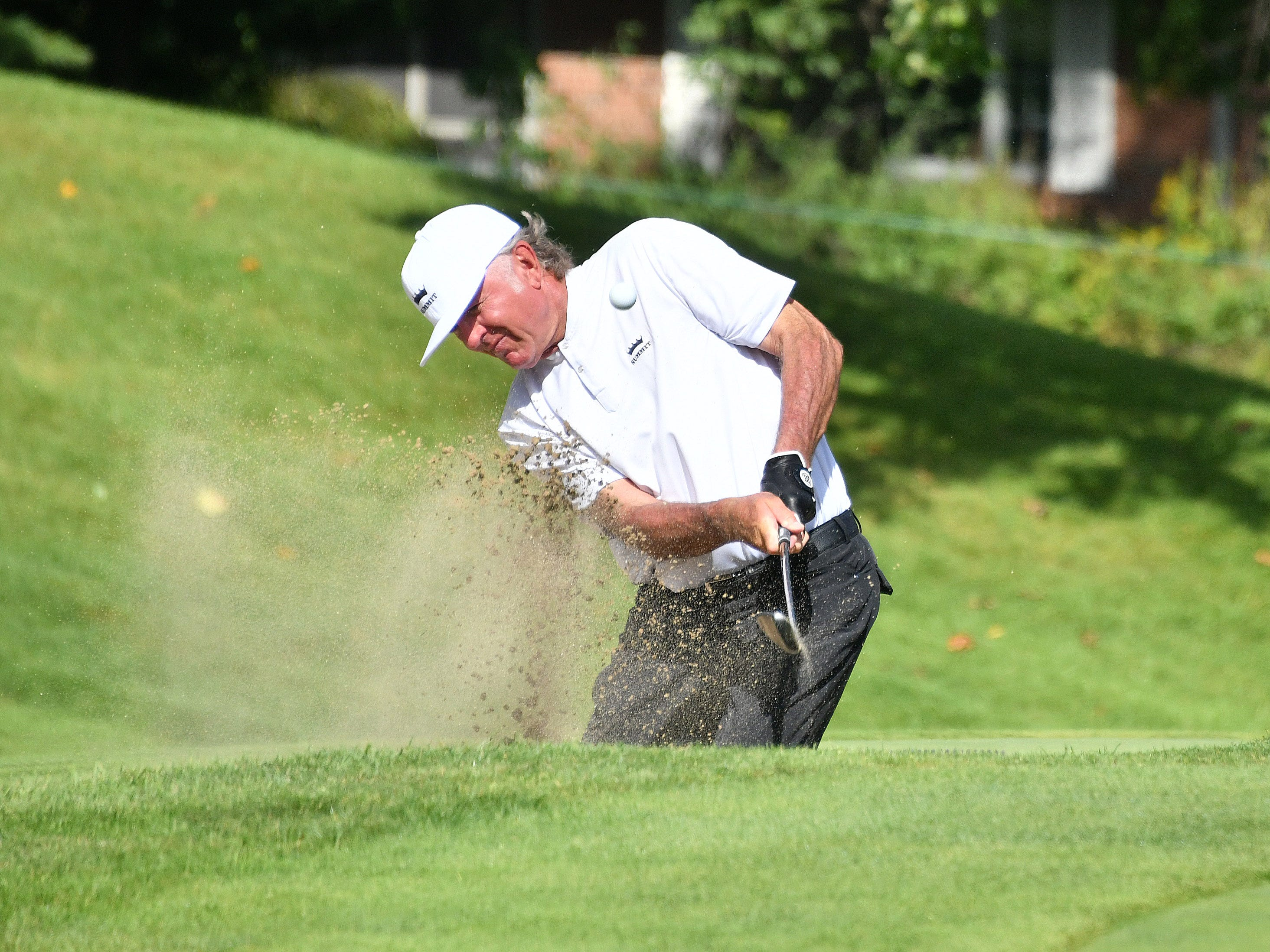 Tommy Armor III hits out of the sand on the first hole.