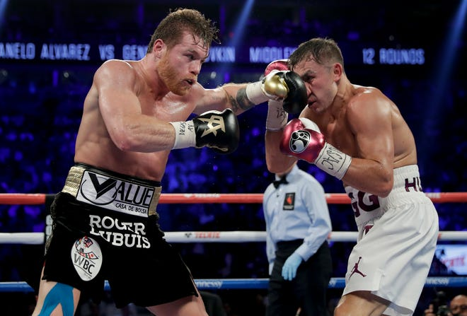 Canelo Alvarez, left, and Gennady Golovkin trade punches in the sixth round during Saturday night's middleweight title boxing match in Las Vegas.