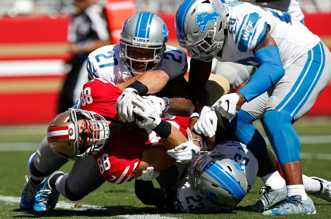 San Francisco 49ers tight end Garrett Celek gets past Detroit Lions safety Glover Quin (27), cornerback Quandre Diggs (28) and cornerback Darius Slay (23) to score a touchdown during the second half.