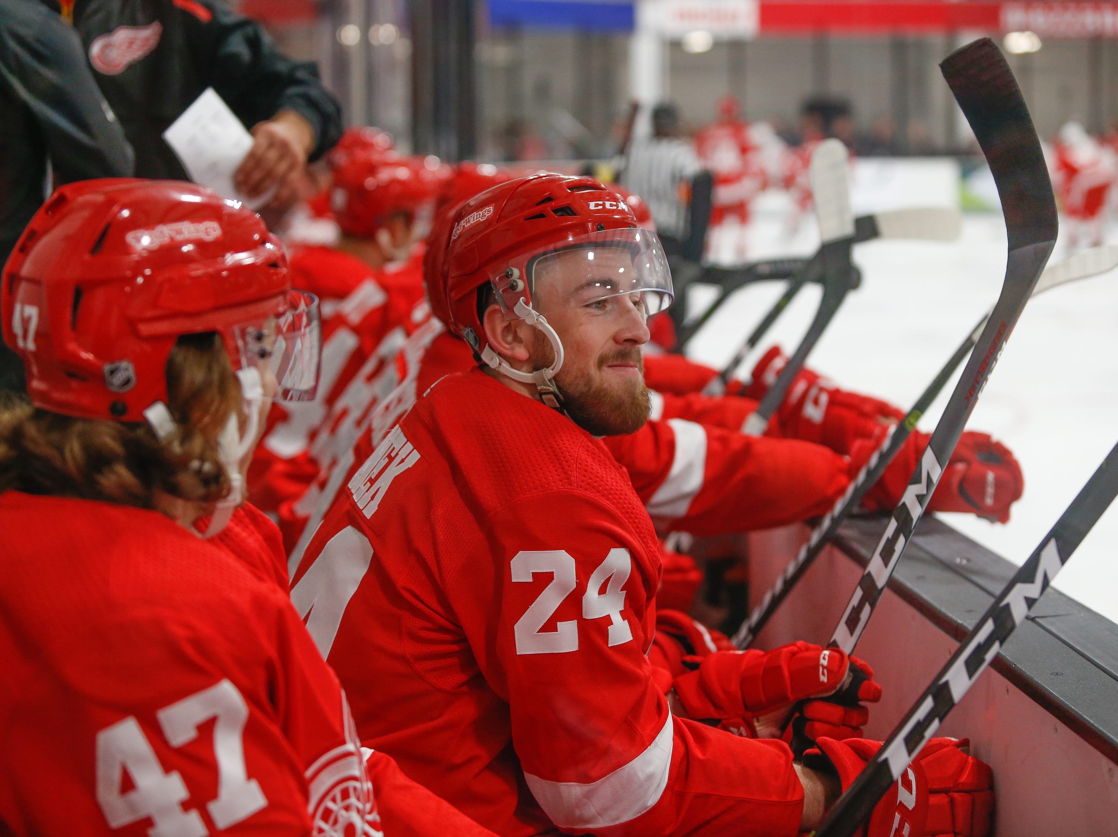 Filip Hronek (24) smiles and surveys the ice from the Team Red bench in the first period.