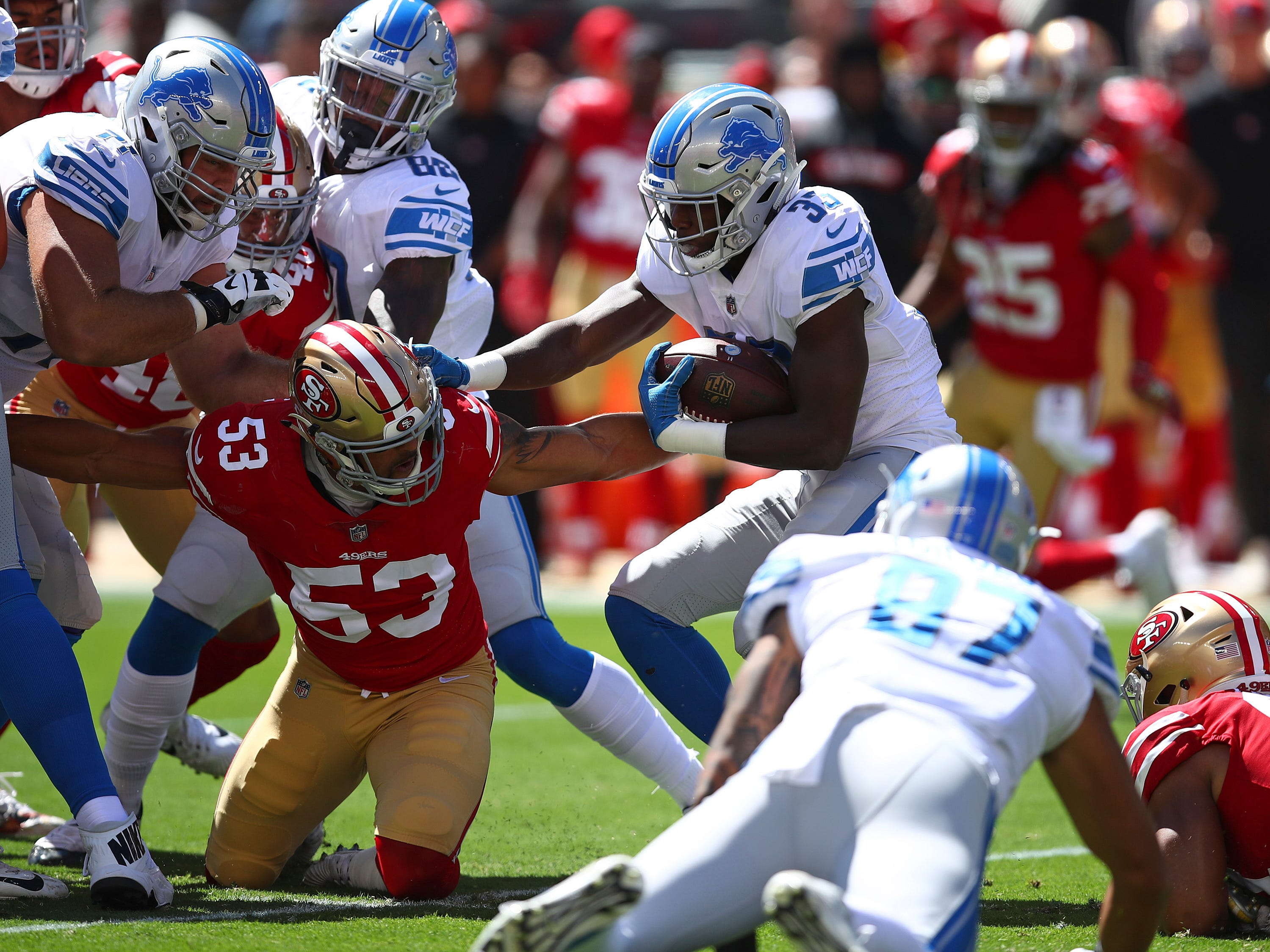 Detroit Lions running back Kerryon Johnson carries the ball as San Francisco 49ers outside linebacker Mark Nzeocha (53) looks on during the first half.